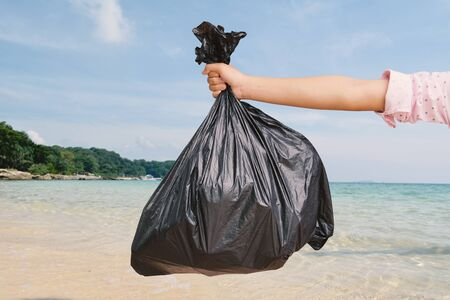 Hand holding plastic bin bag and the sea background, recycling and protect environment from a pollution concept.