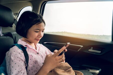 Cute girl in car traveling on holiday.