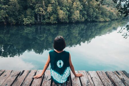 Cute girl sitting on the wood plank resting and looking on the river.