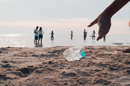 Hand picking bottle plastic on the beach, volunteer to save the environment. Stok Fotoğraf