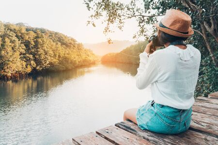 Cute girl enjoy with the nature resting and looking on the river.