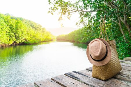 Bamboo bag with a hat on a wood plank and mangrove forest, time to travel on holiday. Stok Fotoğraf