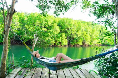 Cute girl enjoy with the nature resting and looking on the river and mangrove forest.