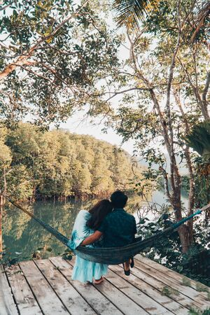 A couple enjoys the natural resting and looking on the river and mangrove forest. Stok Fotoğraf