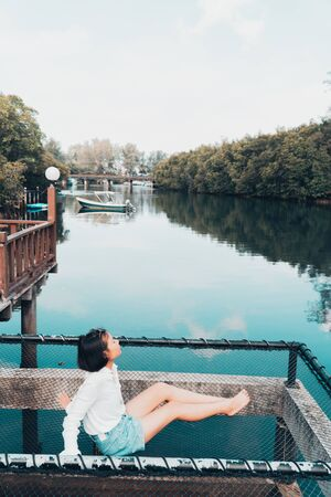 The cute girl enjoys the natural resting and looking on the river and mangrove view.