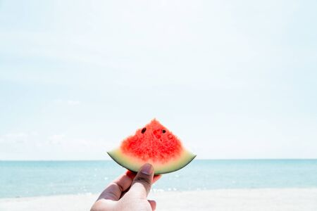 Hand holding piece watermelon with blue sky and sea background.