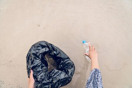 Hand picking up plastic bottle cleaning on the beach, volunteer concept. Stok Fotoğraf