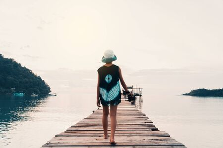 A girl walking on the bridge resting on the sea and holiday to travel concept.