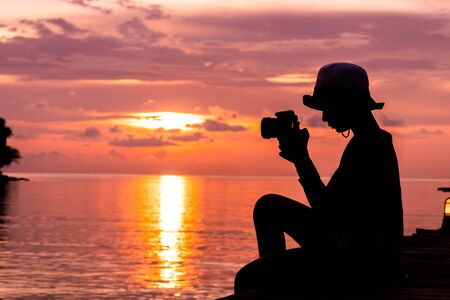 Silhouette of cute girl resting and shooting on the sea and holiday to travel concept. Stok Fotoğraf