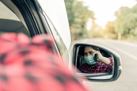A young woman calls insurance while the car is broken.