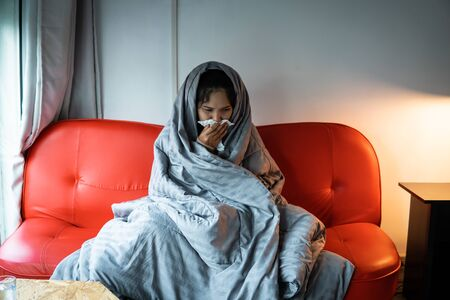 Asian woman have a cold, uses a tissue to cover her mouth when coughing and sneezing at the home, preventing the spread of virus covid 19 ,healthcare concept. selective and soft focus. Stok Fotoğraf