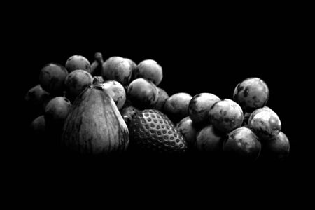 Grapes, fig and strawberry on table with dark background. Still life photography in black and white. Reklamní fotografie