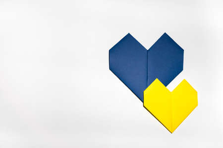 Blue paper heart under smaller yellow paper heart, origami art, on white isolated background. Concept happiness, love.Careful of the heart.