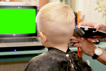 A little boy is cutting a hairdresser in the salon. The kid is watching a cartoon. Green screen on a laptop for signature