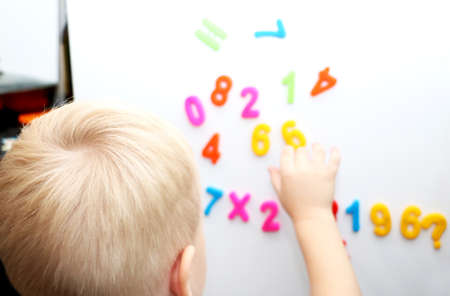 A little boy is studying the magnetic numbers on the fridge. Preschooler training 版權商用圖片
