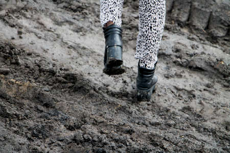 Shoes in the mud. Photo in motion. The concept of provincialism 版權商用圖片
