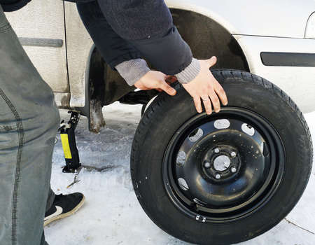 Punched and flat tire on the road. Replacing the wheel with a jack by the driver Banque d'images
