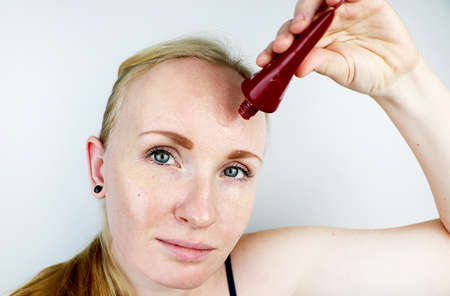 A young woman puts a gel mask on her face. Care for oily, problem skin