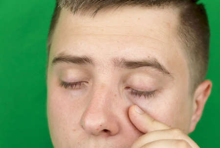 Tears in eyes of crying adult man. Green background. Chromakey