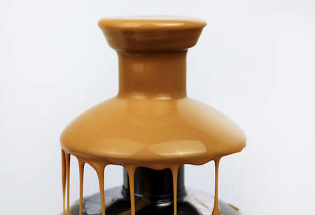 Chocolate fountain of condensed milk, isolated on white background. Delicious Fondue Dessert