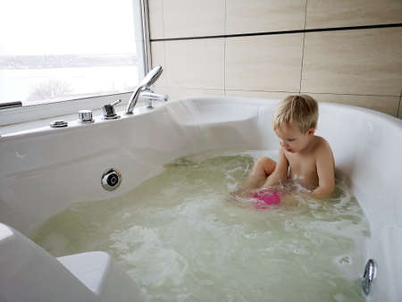 A child in the hot tub. Bath procedures, rest in the hotel. Photos on the phone, mobile photography