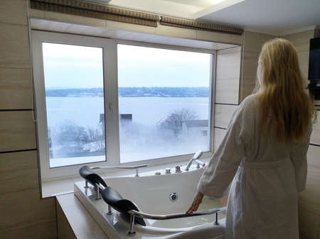 Beautiful woman in a hot tub. Jacuzzi in the hotel, panoramic view from the window in the bathroom Фото со стока