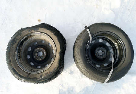 Punched and flat tire on the road. Replacing the wheel with a jack by the driver Фото со стока