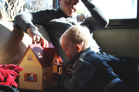Dad and son are playing in the doll house Banco de Imagens
