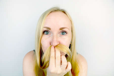 Young blonde girl fooling around, making a mustache out of hair. Studio shooting, laughter