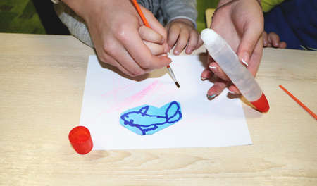 Kids group making arts and crafts in kindergarten. Children spending time in day care centre with the great interest