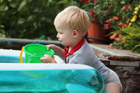 A little boy is playing with water near an inflatable pool. Summer and family holidays. Happy childhood
