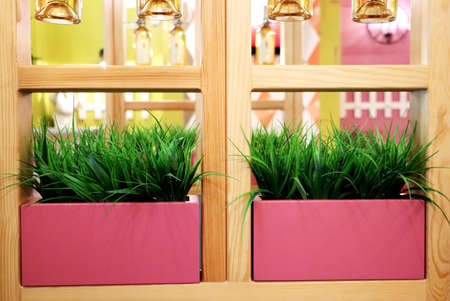 Artificial grass in pink pots. Interior of the restaurant, cafe