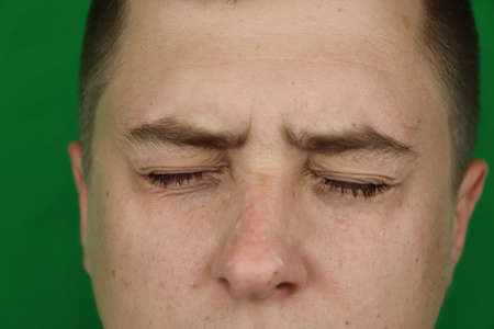 Tears in eyes of crying adult man. Green background. Chromakey Banco de Imagens