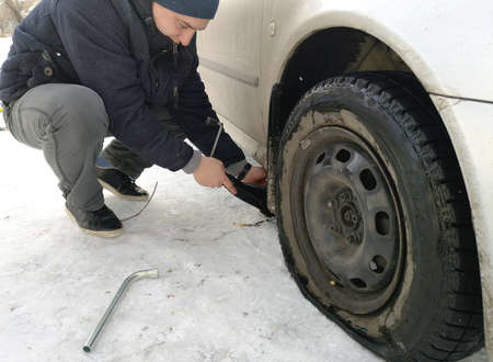 Punched and flat tire on the road. Replacing the wheel with a jack by the driver Banco de Imagens