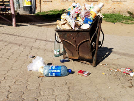 Nikopol, Ukraine, May 20, 2019: a crowded trash can on the Ukrainian street, with garbage on paving slabs. Editorial