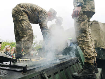 NIKOPOL, UKRAINE - MAY, 2019: Ukrainian military cooks soldiers porridge and treats people to it at the parade in honor of Victory Day. Editorial