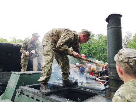 NIKOPOL, UKRAINE - MAY, 2019: Ukrainian military cooks soldiers' porridge and treats people to it at the parade in honor of Victory Day. Banco de Imagens - 124659635