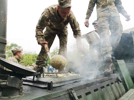 NIKOPOL, UKRAINE - MAY, 2019: Ukrainian military cooks soldiers' porridge and treats people to it at the parade in honor of Victory Day. Banco de Imagens - 124659642