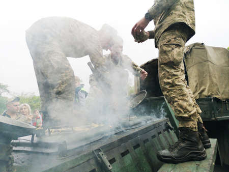 NIKOPOL, UKRAINE - MAY, 2019: Ukrainian military cooks soldiers' porridge and treats people to it at the parade in honor of Victory Day. Banco de Imagens - 124659645