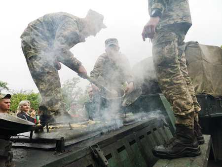 NIKOPOL, UKRAINE - MAY, 2019: Ukrainian military cooks soldiers' porridge and treats people to it at the parade in honor of Victory Day. Banco de Imagens - 124659646
