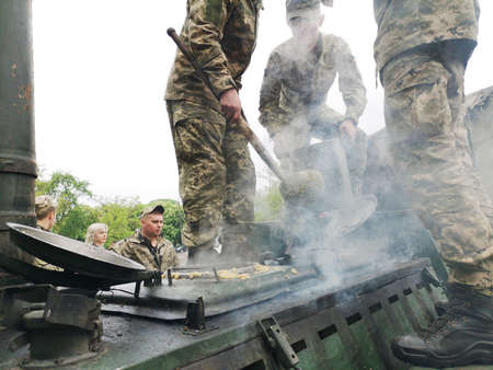 NIKOPOL, UKRAINE - MAY, 2019: Ukrainian military cooks soldiers' porridge and treats people to it at the parade in honor of Victory Day. Banco de Imagens - 124659648
