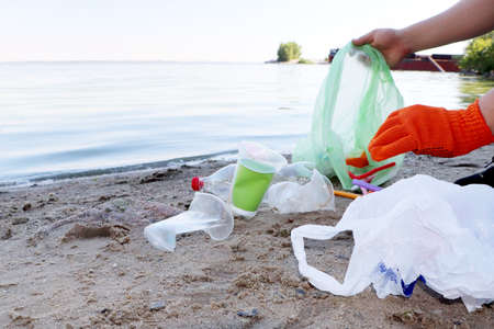 Garbage collection on the beach. Plastic and packages scattered on the beach. A man collects plastic. Ecology protection concept