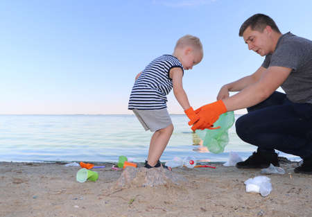 A small child collects trash on the beach. His dad points his finger where to throw garbage. Parents teach children cleanliness. Clean planet concept