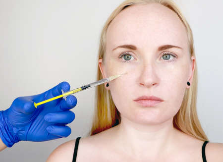 A cosmetologist carries out a procedure - an injection into the face of a young woman. Beauty injections, mesotherapy, hyaluronic acid injections, biorevitalization, cheek correction, fillers