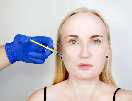 The doctor beautician conducts contour plastic lips: an injection into the lips, lip augmentation. Hyaluronic Acid Injection Fillers