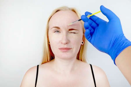 Injection in the forehead, remove the vertical wrinkle. Young woman on reception at the beautician, the procedure of rejuvenation