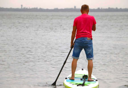 Man on sup board. Water sport, supsurfing. Active weekend at sea, male leisure stand