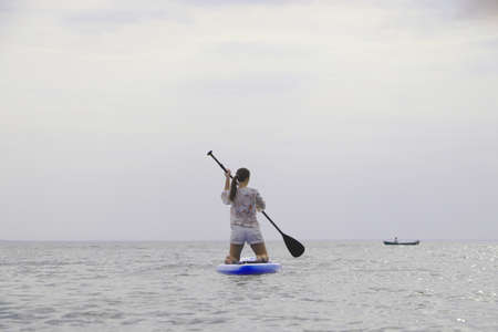 Girl on sup board. Water sport, supsurfing. Active weekend at sea, woman leisure stand