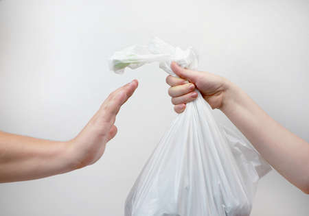 Refusal of a plastic bag. Environmental protection concept. An offer in a store to buy goods in a package, a man refuses with a stop gesture. Isolated on white background, place for an inscription Zdjęcie Seryjne