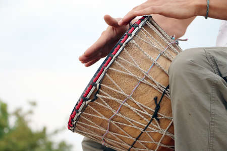 A man plays an African djembe drum against a blue sky. Creativity, rest and relaxation. Ethnic musical instrument against the sky as a concept of creative flight.